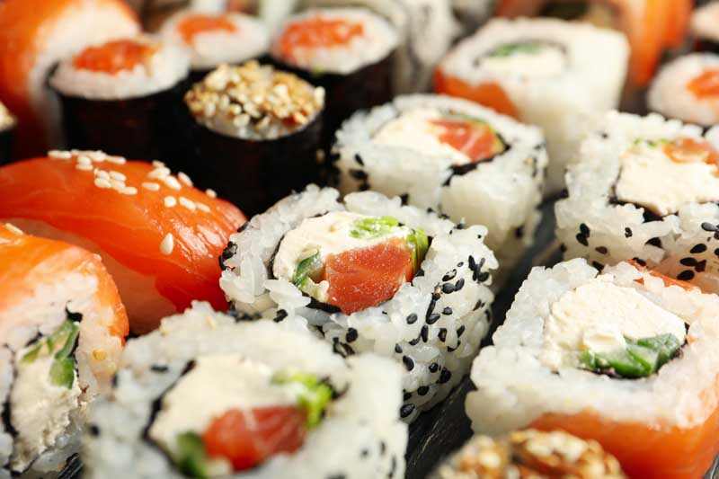 Delicious sushi rolls on wooden background, close up Japanese food